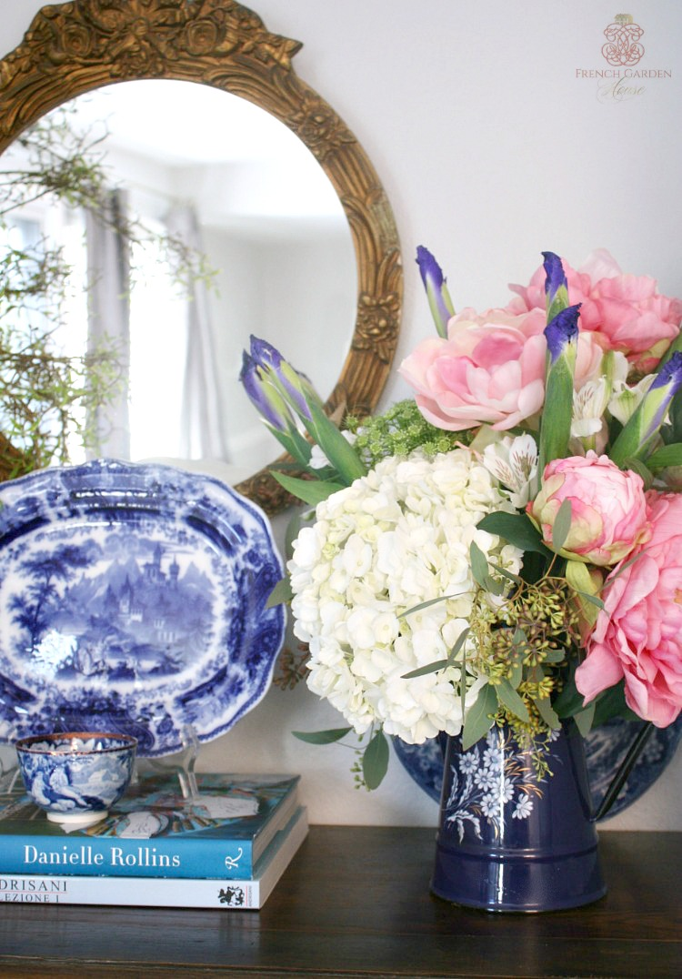 blue and white on a mantel with pink peonies