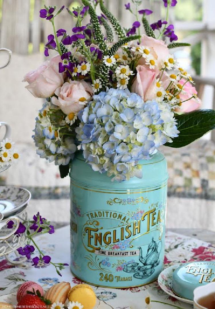floral arrangement in aqua tea tin